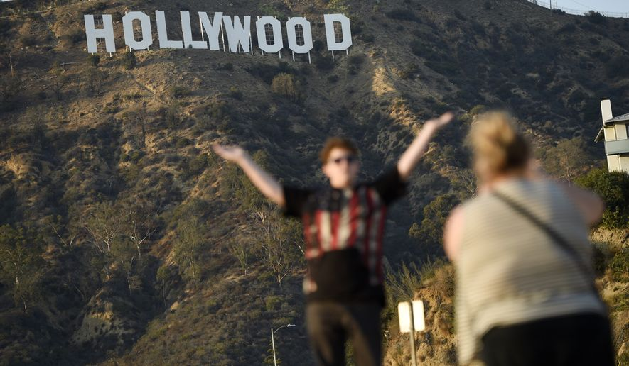 Tourists pose in front of The Hollywood Sign on Tuesday, Aug. 23, 2016, in Los Angeles. (Photo by Chris Pizzello/Invision/AP)
