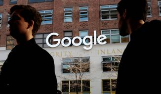 In this Dec. 4, 2017, photo, people walk by Google offices in New York. (AP Photo/Mark Lennihan)