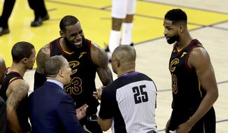 Cleveland Cavaliers forward LeBron James (23) and head coach Tyronn Lue, bottom, talk with referee Tony Brothers (25) during the second half of Game 1 of basketball's NBA Finals against the Golden State Warriors in Oakland, Calif., Thursday, May 31, 2018. (AP Photo/Marcio Jose Sanchez) **FILE**