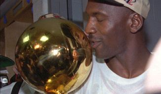 Michael Jordan of the Chicago Bulls kisses the NBA championship trophy after the Bulls defeated the Seattle SuperSonics 87-75 to win the NBA Championship Sunday, June 16, 1996, in Chicago.  (AP Photo/Mike Fisher)