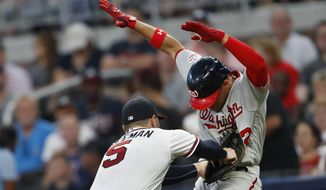 Washington Nationals' Juan Soto (22) is tagged out by Atlanta Braves first baseman Freddie Freeman after hitting a slow-rolling ground ball during the third inning of a baseball game Thursday, May 31, 2018, in Atlanta. (AP Photo/John Bazemore)