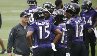 Baltimore Ravens head coach John Harbaugh, left, speaks with wide receivers Michael Crabtree (15), John Brown (13) and Jaleel Scott (12) during an NFL football organized team activity at the team's headquarters in Owings Mills, Md., Thursday, May 31, 2018. (AP Photo/Patrick Semansky) **FILE**