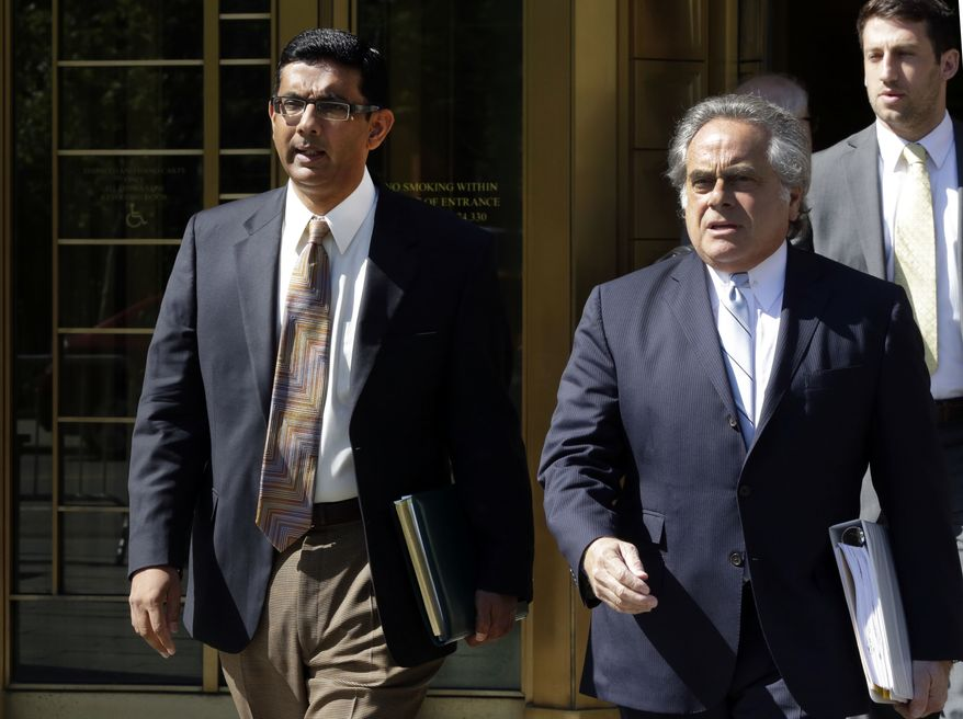 Conservative scholar and filmmaker Dinesh D'Souza, left, accompanied by his lawyer Benjamin Brafman leaves federal court, in New York. President Donald Trump says he will pardon conservative commentator Dinesh D'Souza who pleaded guilty to campaign finance fraud. Trump tweeted Thursday: Will be giving a Full Pardon to Dinesh DSouza today. He was treated very unfairly by our government! DSouza was sentenced in 2014 to five years probation after he pleaded guilty to violating federal election law.  (AP Photo/Richard Drew)