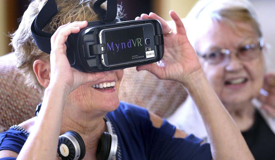 ADVANCE FOR USE MONDAY, JUNE 4 - In this May 23, 2018 photo, Kathy Helgerson gets a virtual reality headset ready for a demonstration during a visit to Brookdale Assisted Living in La Crosse, Wis. Helgerson runs Simple Steps to Technology, helping seniors with Skype, smartphones and computers.(Peter Thomson/La Crosse Tribune via AP)