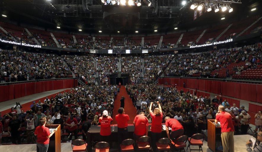 FILE - In this May 22, 2018, file photo, members of the Culinary Workers Union, Local 226, assemble for a presentation at a university arena before an evening vote on whether to authorize a strike in Las Vegas. The two largest resort operators in Las Vegas would lose more than $10 million a day combined if housekeepers, cooks and others go on strike, a possibility starting Friday, the union representing thousands of casino workers said, Thursday, May 31, 2018. (Steve Marcus/Las Vegas Sun via AP, File)
