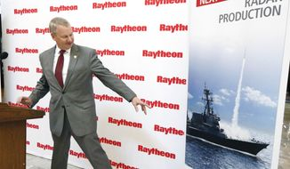 Wes Kramer, president of Raytheon's Integrated Defense Systems business, points to the radar housing on a U.S. Navy war ship poster, Thursday, May 31, 2018, and says his company plans to invest $100 million in its Forest, Miss., plant, to test and make military radars, during a news conference at the Capitol in Jackson, Miss. In addition, Raytheon will construct a new 50,000-square-foot facility to serve as the hub for testing, integration and production of s-band radars, including the U.S. Navy's next -generation SPY-6, Air and Missile Defense Radar program. (AP Photo/Rogelio V. Solis)