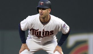 FILE - In this April 12, 2018, file photo, Minnesota Twins' Joe Mauer takes a lead at first in the team's baseball game against the Chicago White Sox in Minneapolis. Mauer has not been able to shake the concussion-like symptoms he has been experiencing since hurting his neck three weeks ago. Mauer's return to the lineup hit another roadblock while working out Thursday, May 31, before Minnesota's game against Cleveland, with more sensitivity to light and noise. The 35-year-old has also been dealing with a cervical strain resulting from a dive for a foul ball on May 11. He played for another week before departing mid-game on May 18. (AP Photo/Jim Mone, File)