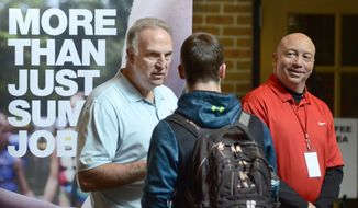In this March 14, 2018, file photo, Dan Cieslak, left, a Human Resources representative for the Dunham's Distribution Center, and Warren Whitlow, a training manager, speak to students and other visitors during the Experience Indiana job fair event in the student center at Indiana Wesleyan University in Marion, Ind. The U.S. government issues the May jobs report on Friday, June 1. (Jeff Morehead/The Chronicle-Tribune via AP, File)