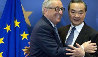 European Commission President Jean-Claude Juncker, left, prepares to shake hands with China's Foreign Minister Wang Yi prior to a meeting at EU headquarters in Brussels, Friday, June 1, 2018. The European Union and China say they will deepen ties on trade and investment and that they fully support global trade rules, after U.S. President Donald slapped tariffs on steel and aluminum imports. (AP Photo/Virginia Mayo)