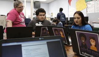 In this Friday, May 18, 201 photo, Fran Bromley-Norwood, a teacher at Cheyenne High School, checks 12th-grade student Ricardo Torres' and 11th-grade student Ivette Para's classwork during cyber defense class in Las Vegas. (Bizuayehu Tesfaye/Las Vegas Review-Journal via AP)