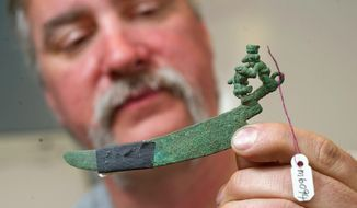 In this Tuesday, May 8, 2018 photo, imaging technician Greg Doolittle holds a moche horizontal knife from Peru at Valley Inspection Service in Allentown, Pa. Doolittle has been performing non-destructive high power x-ray imaging to study 100 Peruvian objects that are owned by a private collector in New York City. The work is a joint research study organized by retired Lehigh University professor Michael Notis, professor Aaron Shugar of Buffalo State University, and by Dr. Dong Ning Wang, an adjunct professor at Lehigh. (Harry Fisher/The Morning Call via AP)