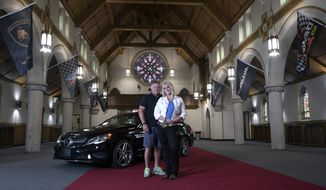 In a May 23, 2018 photo, Kimberly Phillips and Mike Fanto, co-owners of the Holy Grail Auto Garage in East Pittsburgh, pose for a portrait. The new auto storage facility is in the former St. Helen Catholic church. (Nate Guidry/Pittsburgh Post-Gazette via AP)