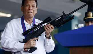 FILE - In this Thursday, April 19, 2018, file photo, Philippine President Rodrigo Duterte jokes to photographers as he holds an Israeli-made Galil rifle at Camp Crame in suburban Quezon city northeast of Manila, Philippines. The author of the first biography of Rodrigo Duterte says the maverick Philippine president is gravitating toward China partly because of a personal animosity toward the United States and its criticism of his human rights record. (AP Photo/Bullit Marquez, File)