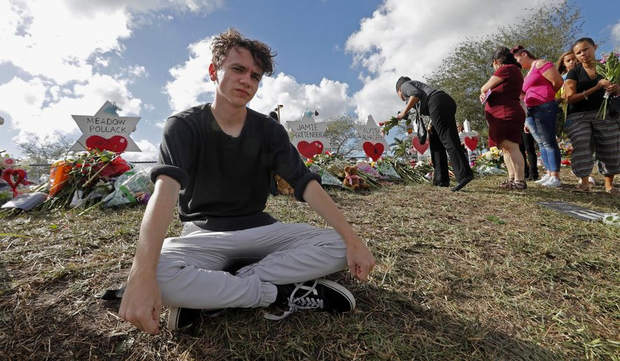 FILE- In this Feb. 19, 2018, file photo, Chris Grady, a student at Marjory Stoneman Douglas High School, sits at a memorial  in Parkland, Fla., for those slain in the Feb. 14 school shooting. Grady who had planned to join the U.S. Army before the shooting, has withdrawn his enlistment and will now work for the March for Our Lives movement. (AP Photo/Gerald Herbert, File)