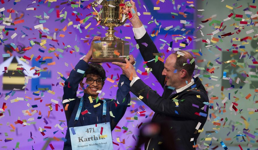 Karthik Nemmani, 14, from McKinney, Texas, is presented with the Scripps National Spelling Bee trophy by Adam Symson, president and CEO, E.W. Scripps Company, after he won the bee, in Oxon Hill, Md., Thursday, May 31, 2018. (AP Photo/Cliff Owen)