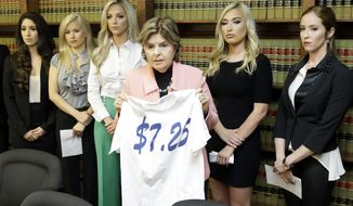 Attorney Gloria Allred stands among former Houston Texans cheerleaders, from left, Ashley Rodriguez, Morgan Wiederhold, Kelly Neuner, Hannah Turnbow, and Ainsley Parish, right, while holding up a shirt printed with $7.25, the amount she says the former cheerleaders where paid per hour, as she speaks during a press conference Friday, June 1, 2018, in Humble, Texas, announcing a lawsuit on behalf of the five the former cheerleaders at the law offices of Kimberley Spurlock. The five former cheerleaders are suing the NFL franchise, alleging the team failed to fully compensate them as required by law and subjected them to hostile work environment in which they were harassed, intimidated and forced to live in fear.(Melissa Phillip/Houston Chronicle via AP)