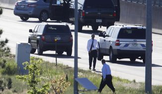 Denver Police Department detectives, foreground, investigate near where a Nissan sedan, top left, being driven by an Uber driver crashed into a retaining wall along Interstate 25 south of downtown Denver early Friday, June 1, 2018. The driver allegedly shot and killed a passenger at 2:45 a.m. after a confrontation broke out between the two while headed southbound on the interstate. (AP Photo/David Zalubowski)
