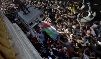 Palestinian mourners carry the body of a volunteer paramedic Razan Najjar, 21, into her family house during her funeral in town of Khan Younis, southern Gaza Strip, Saturday, June 2, 2018. Najjar was killed by Israeli fire Friday during mass protests in the Gaza Strip, the Palestinian Health Ministry said. (AP Photo/Khalil Hamra)