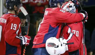 Washington Capitals forward Alex Ovechkin, center, of Russia, celebrates with goaltender Braden Holtby, right, after the team's 3-1 victory over the Vegas Golden Knights in Game 3 of the NHL hockey Stanley Cup Final, Saturday, June 2, 2018, in Washington. At left is Capitals forward Nicklas Backstrom, of Sweden. (AP Photo/Alex Brandon)