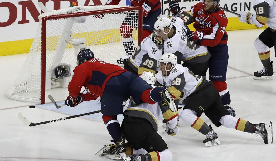 Washington Capitals forward Alex Ovechkin, left, of Russia, goes over -Vegas Golden Knights defenseman Brayden McNabb to score a goal during the second period in Game 3 of the NHL hockey Stanley Cup Final, Saturday, June 2, 2018, in Washington. (AP Photo/Pablo Martinez Monsivais)