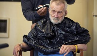 In this Tuesday, May 22, 2018 photo, Bob Davis, 78, receives a haircut from Yakima Neighborhood Health Services' Jesus Campos, respite-housing case manager, at a respite unit in Yakima, Wash. Davis suffers from dementia and has been shuffled between different service providers, the hospital and police before finally ending up in the care of Yakima Neighborhood Health Services. (Shawn Gust/Yakima Herald-Republic via AP)