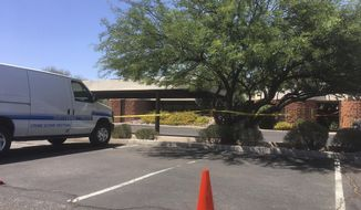 A Scottsdale police vehicle and crime scene tape is seen outside the Scottsdale, Ariz., building where a man was found shot to death on Saturday, June 2, 2018. Police are looking into whether this homicide is connected to the shooting deaths of a well-known forensic psychiatrist, Dr. Steven Pitt, and two paralegals. (AP Photo/Paul Davenport)