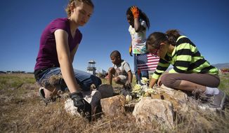 In this May 26, 2018, photo, Lynnea Crook, Garrett Crook, Sariah Crook and Evaine Ha'o pull weeds from around a grave as Hawaiians descendants gather to clean the graves of their ancestors on Memorial Day in Iosepa, Utah. The Utah town ghost founded over a hundred years ago by Pacific Islanders who converted to the Mormon church is still visited every year by descendants who celebrate and decorate their ancestors' gravesites. (Trent Nelson/The Salt Lake Tribune via AP)