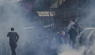 Kashmiri men left, carry body of Qaiser Amin Bhat, amid tear gas smoke fired by Indian police men after they stopped the funeral procession in Srinagar, Indian controlled Kashmir, Saturday, June 2, 2018. Government forces in Indian-controlled Kashmir Saturday fired shotgun pellets and tear gas at hundreds of mourners in the disputed region's main city as they carried the body of a young man killed the other day after a paramilitary vehicle run over him, police and residents said. (AP Photo/Dar Yasin)