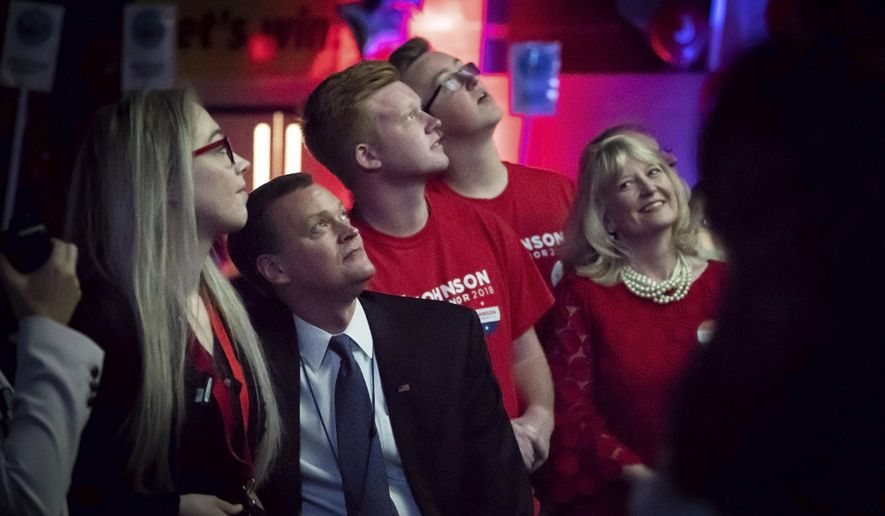 Sondi Johnson, right, looks over at her husband Jeff and smiles as they watched a promotional video about Jeff's life and candidacy as their sons Thor and Rolf, look on, Saturday, June 2, 2018 in Duluth, Minn. Democrats kicked off their statewide endorsing convention Friday in Rochester as Republicans gathered in Duluth. Both parties are considering candidates running for U.S. Senate, Attorney General and other statewide offices, but the main focus is on the race to replace outgoing Democratic Gov. Mark Dayton.  (Glen Stubbe/Star Tribune via AP)