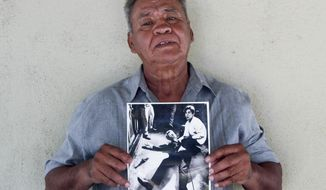 "In this undated photo provided by StoryCorps, Juan Romero, 67, holds a photo of himself and the dying Sen. Robert F. Kennedy at the Ambassador Hotel in Los Angeles, taken by the Los Angeles Times' Boris Yaro on June 5, 1968, at his home in Modesto, Calif. Associated Press Hollywood reporter Bob Thomas was on a one-night political assignment covering Sen. Robert F. Kennedy's victory celebration in the California presidential primary at the Ambassador Hotel when mayhem unfolded before his eyes. He heard pops of gunfire, then screams, and quickly rushed into the kitchen to see the dying Kennedy on the floor, blood oozing from his head. He found a phone and called the AP desk. ""I've got a flash. Kennedy shot."" Sirhan Sirhan was later convicted of Kennedy's murder. (Jud Esty-Kendall/StoryCorps via AP)"
