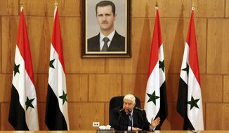 In this photo released by the Syrian official news agency SANA, Syrian Foreign Minister Walid al-Moallem sits beneath a portrait of Syrian President Bashar Assad as he speaks during a press conference in Damascus, Syria, Saturday, June 2, 2018. Al-Moallem said Iranian military advisers are embedded with Syrian troops but Tehran has no combat forces or fixed bases in the country. (SANA via AP)