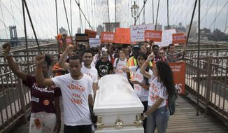 Demonstrators carry a coffin over the Brooklyn bridge during a march and rally against gun violence, Saturday, June 2, 2018, in New York. Youth Over Guns, a gun violence prevention organization in New York City, lead a march across the Brooklyn Bridge to call for youth empowerment and investment in urban communities to end gun violence. (AP Photo/Mary Altaffer)
