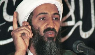 FILE--Exiled Saudi dissident Osama bin Laden speaks in 1998 at a meeting at an undisclosed location in Afghanistan, according to the source, in this file photo. Bin Laden, in a statement mostly made up of quotations from the Quran and sayings of the Prophet Muhammad, called on Pakistanis Thursday, Oct. 1, 2001, to ``make Islam victorious,'' saying the government there has chosen to stand ``under the banner of the cross,'' in a statement sent to the Qatari-based Al-Jazeera satellite channel. In the background is a banner with a verse from the Quran, Islam's holy book. (AP Photo/File)