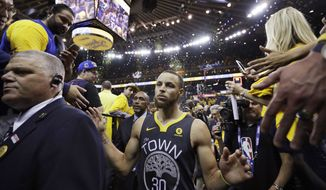 Golden State Warriors guard Stephen Curry walks past fans after Game 2 of basketball's NBA Finals between the Warriors and the Cleveland Cavaliers in Oakland, Calif., Sunday, June 3, 2018. The Warriors won 122-103. (AP Photo/Marcio Jose Sanchez)