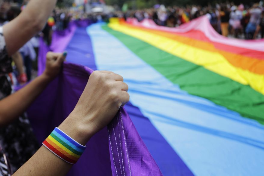 Revelers at the annual gay pride parade hold up a giant rainbow flag in Sao Paulo, Brazil, Sunday, June 3, 2018. (AP Photo/Nelson Antoine) ** FILE **