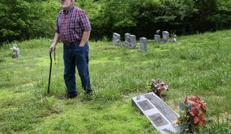 In this May 21, 2018, photo, Jim DeMoss walks around the grave of his parents and where he plans on burying his brother at the DeMoss Family Cemetery in Nashville, Tenn. Decades after crashing in Hawaii the remains of Harold DeMoss, a World War II pilot, have been positively identified. (Lacy Atkins/The Tennessean via AP)