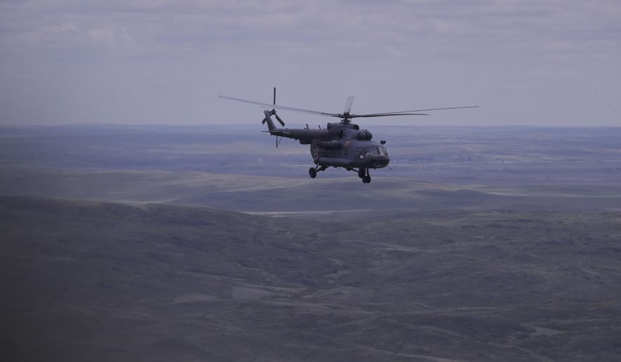 A Russian search and rescue team helicopter flies from the Kazakh town of Karaganda to Dzhezkazgan, on the eve of Russian Soyuz MS space capsule landing, Kazakhstan, Kazakhstan, Sunday, June 3, 2018. The return of the Soyuz space capsule with Russian cosmonaut Anton Shkaplerov, U.S. astronaut Scott Tingle, and Japanese astronaut Norishige Kanai, crew members of the mission to the International Space Station, ISS is scheduled on Sunday, June 3, 2018. (AP Photo/Dmitri Lovetsky, Pool)