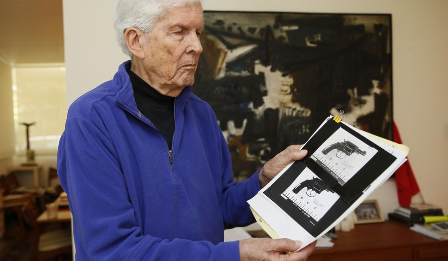 In this Thursday, May 31, 2018, photo, Sen. Robert Kennedy aide Paul Schrade holds an evidence photo of gunman Sirhan Sirhan's revolver with the eight expended shell casings found in the chamber, and the Weisel, Goldstein, and Kennedy bullets, at his home in Los Angeles. When a gunman open fire toward Sen. Robert Kennedy, the first bullet missed the senator and struck Kennedy aide Paul Schrade in the head. Schrade woke up the next day and found out the Democratic presidential candidate was dead. Today, Schrade believes the Los Angeles Police botched the case and failed to investigate possible leads about a second gunman. (AP Photo/Damian Dovarganes)