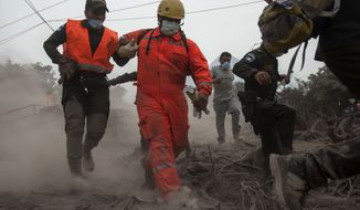 """Firefighters and police are forced to evacuate a search and rescue effort as the Volcan de Fuego, or """"Volcano of Fire,"""" continues to spill out smoke and ash in Escuintla, Guatemala, Monday, June 4, 2018. A fiery volcanic eruption in south-central Guatemala sent lava flowing into rural communities killing dozens. (AP Photo/Oliver de Ros)"""