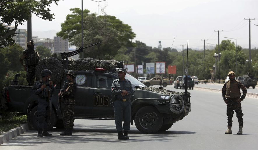 Security personnel inspect the site of a deadly suicide attack in Kabul, Afghanistan, Monday, June 4, 2018. A suicide bombing targeted a gathering of Afghanistan's top clerics on Monday in Kabul, killing at least seven people and wounding nine. (AP Photo/Rahmat Gul)