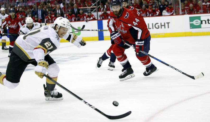 Vegas Golden Knights forward Cody Eakin (21) chases the puck in front of Washington Capitals defenseman Brooks Orpik (44) during the first period in Game 4 of the NHL hockey Stanley Cup Final, Monday, June 4, 2018, in Washington. (AP Photo/Alex Brandon)