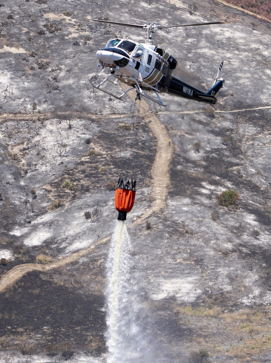 A helicopter from the Fresno County Fire Department makes a water drop on the remnants of a brush fire in Wood Canyon in the hills below Soka University in Aliso Viejo, Calif., Sunday, June 3, 2018. The Orange County Fire Authority said Sunday that the 150-acre blaze is 10 percent contained after churning through thick underbrush that hasn't burned in years. (Leonard Ortiz/Orange County Register/SCNG via AP)