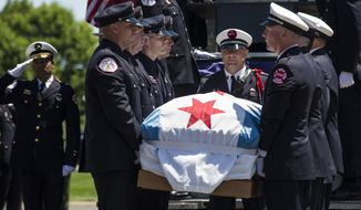 Chicago Fire Department personnel lift Juan Bucio's casket off a fire truck for his funeral at St. Rita of Cascia High School, Monday, June 4, 2018. Bucio, a CFD diver, died on Memorial Day while conducting a search for a boater who fell overboard in the Chicago River. (Ashlee Rezin/Chicago Sun-Times via AP)