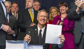 Illinois Governor Bruce Rauner displays the signed Illinois state budget for fiscal year 2019, Monday, June 4, 2018, in Chicago. It is the first full-year spending plan he's enacted since taking office in 2015. The Republican, who's seeking re-election in November, was joined at Monday's bill signing by legislators from both parties who hailed the budget as a bipartisan compromise. (Tyler LaRiviere/Sun Times via AP)