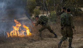 An Israel soldier extinguishes a fire started by a kite with attached burning cloth launched by Palestinians from Gaza, a near the Israel and Gaza border, Friday, June 1, 2018. (AP Photo/Tsafrir Abayov)