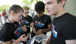 """A group of Marjory Stoneman Douglas High School students tweet out information after a news conference, Monday, June 4, 2018, in Parkland, Fla. A day after graduating from high school, the group of Florida school shooting survivors has announced a multistate bus tour to """"get young people educated, registered and motivated to vote."""" (AP Photo/Wilfredo Lee)"""