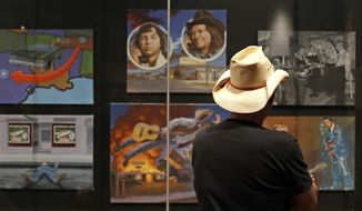 In this May 25, 2018 photo, a visitor to the Country Music Hall of Fame and Museum in Nashville, Tenn., views the the Outlaws & Armadillos exhibit. The new museum exhibit offers a deeper dive behind the poets, pickers and characters that revolutionized country music in the 1970s. (AP Photo/Mark Humphrey)