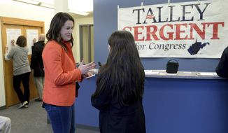 In a March 1, 2018 photo, Democrat Talley Sergent talks to a supporter inside her campaign headquarters in Charleston, W.Va. She is running for Congress in West Virginia's 2nd District against incumbent Republican Alex Mooney. (Chris Dorst/Charleston Gazette-Mail via AP)
