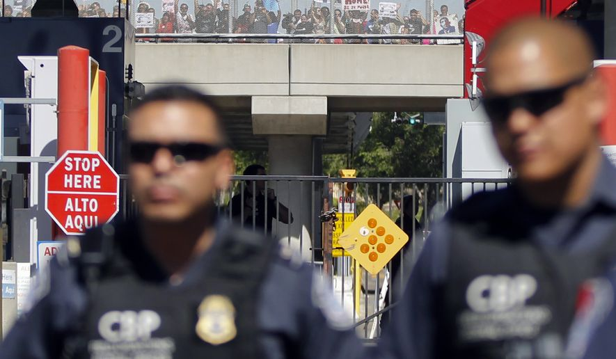 Demonstrators supporting the group Border Dreamers and other advocates for an open border policy hold signs while lining a walking bridge inside United States behind Customs and Border Protection officers who are blocking the vehicle entrance to the United States Monday, March 10, 2014, in Tijuana, Mexico. (AP Photo/Lenny Ignelzi )