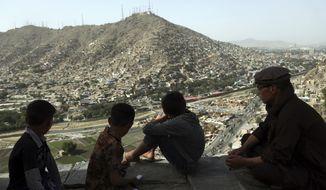 Afghan boys look out over the city of Kabul, Afghanistan, Tuesday, June 5, 2018. (AP Photo/Rahmat Gul) ** FILE **